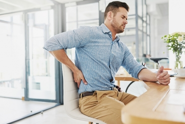 A man holds his back because it is in pain while sitting at his work desk.