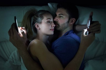 man and woman on cellphones in bed together