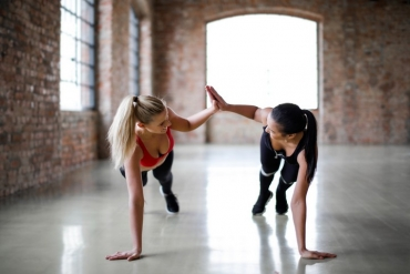 Two women do one handed pushups and high-five with the other hand.