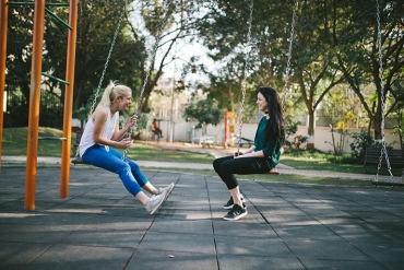 two female friends talking on swings at park