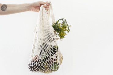 Person holding a reusable grocery bag with veggies in it in front of a white wall.