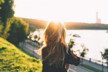 Blonde woman standing alone on a hill in front of a beautiful scene and a bright sun.