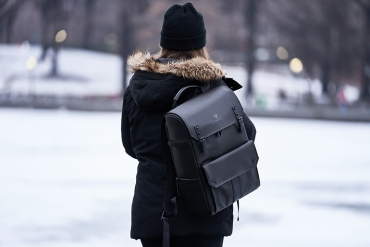 A woman is standing in the snow with a black leather backpack on. She is wearing all black and is facing away from the camera so that the backpack is the focus.