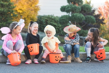 Kids dressed up for Halloween, sitting on a curb checking out their candy.