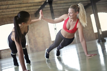 two woman exercising and high fiving