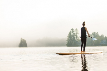 woman stand up paddle boarding on calm waters