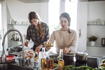 Two sisters cook a vegan holiday dinner together in a beautiful kitchen.