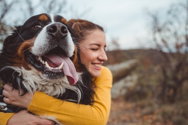 A woman wearing yellow hugs her dog while he pants.