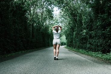 Woman running down a road in the middle of a beautiful lush green Forrest.