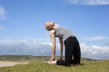 A women stretches in camel pose on a hillside.