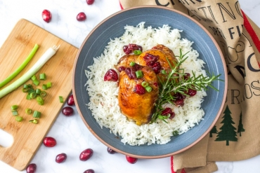 Delicious cranberry balsamic chicken on a plate of rice.