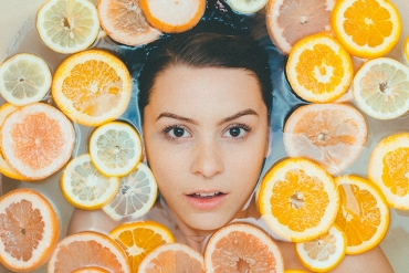 A woman taking a hydrating bath surrounded by oranges and citrus.