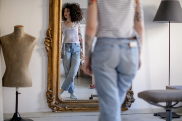A woman stands in front of a mirror looking at her body.