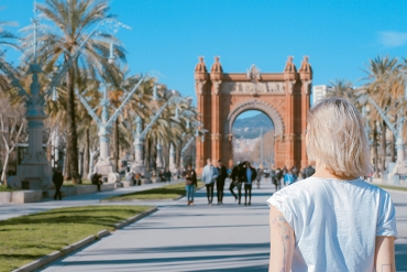 A woman is in barcelona, spain facing a monument. She has white blonde hair and a tattoo of a star on her arm.