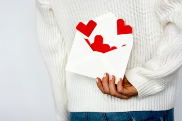 person holding envelop with hearts coming out of it behind their back