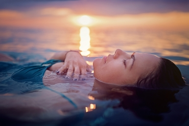 close up of relaxed woman meditating in water
