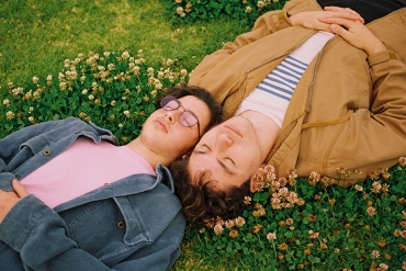 Two friends lay in the grass next to some yellow flowers with their eyes closed.