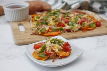 Nachos made with sweet potato chips. One serving is put on a separate plate in front of a baking tray of nachos.