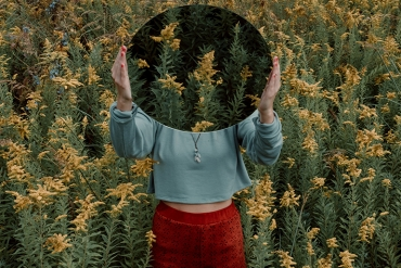 Woman standing in a hemp field holding a mirror in front of her face.