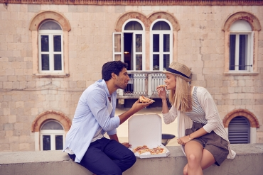 couple eating pizza while traveling