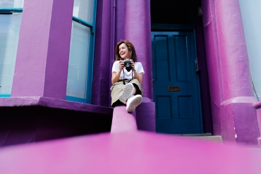 Woman sitting with her camera on purple steps outside a purple building.
