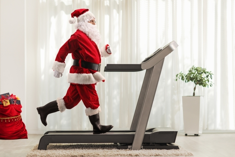 A santa person is running on a treadmill at home.
