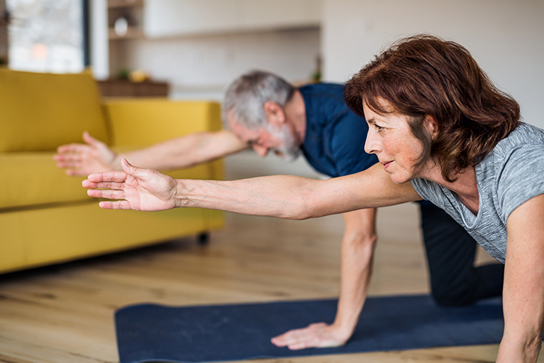 An elderly couple doing low impact exercises.