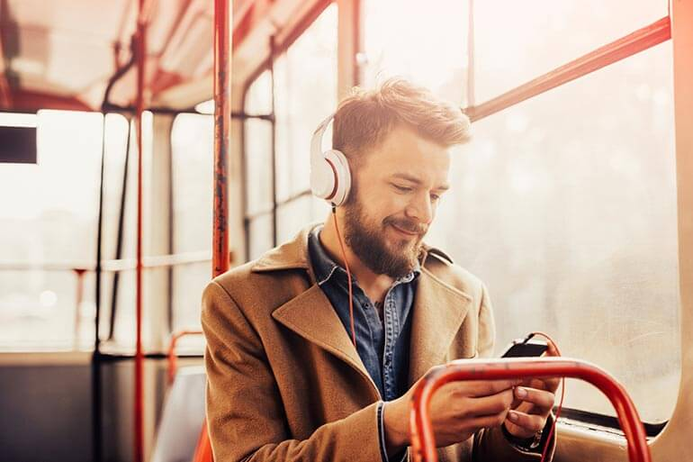 man listening to podcast on bus during morning commute