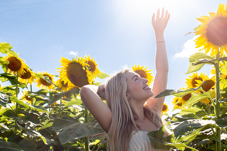 Woman dancing in sunflowers.