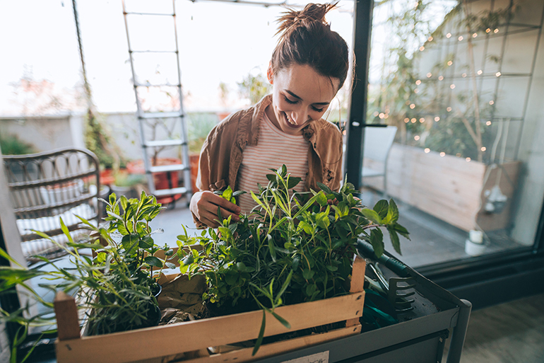 Woman adding compost to plants.