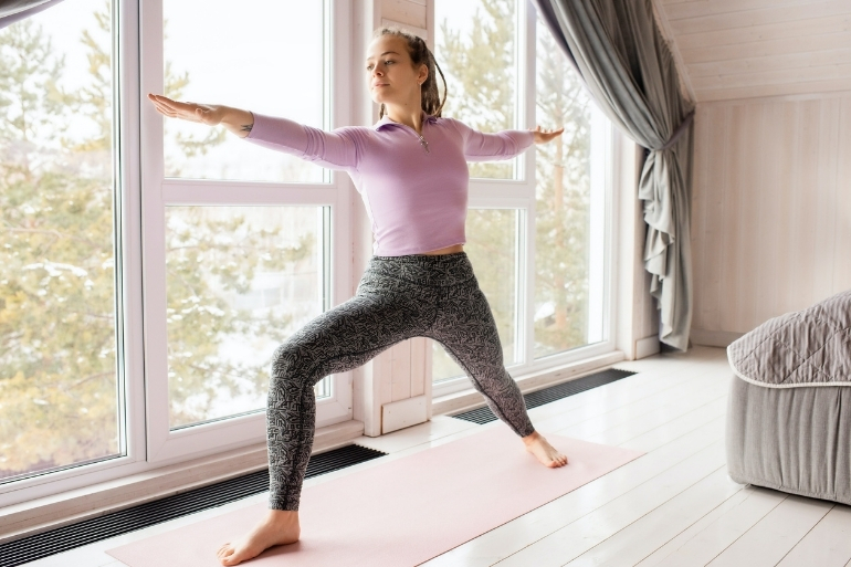 A person doing yoga at home. She is standing on a yoga mat doing warrior one pose.