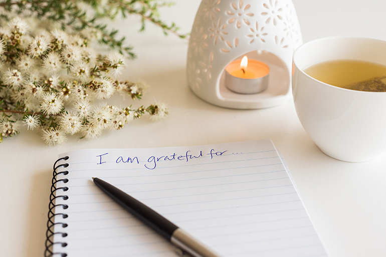 "Someone has written ""I am grateful"" on a piece of paper next to a candle and a cup of tea."