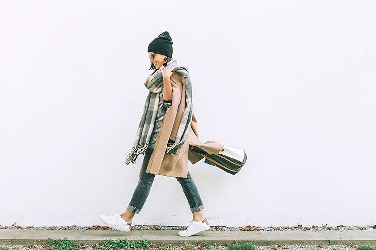 Cozy woman walking while wearing sustainable clothes in autumn.