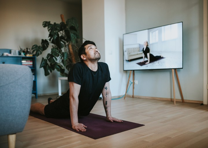 A man practices yoga in his living room while taking a class online.