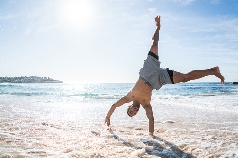 man doing cartwheel on the beach