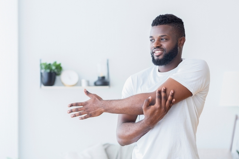 A man stands and stretches his arms in order to improve his health and flexibility.