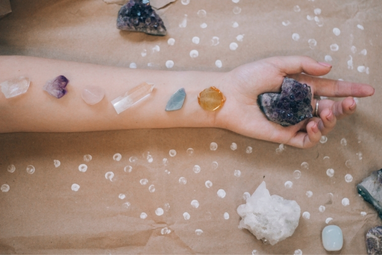 A person uses crystals to balance their chakras.