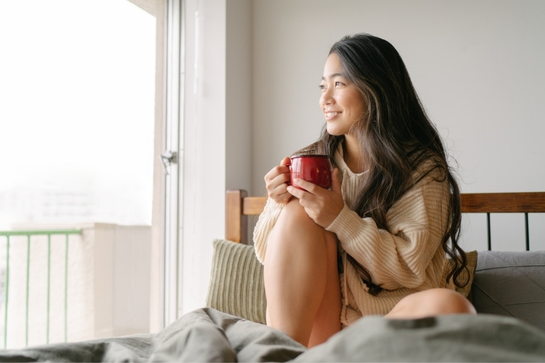 A woman sits on her bed drinking coffee in the morning and looking out the window.