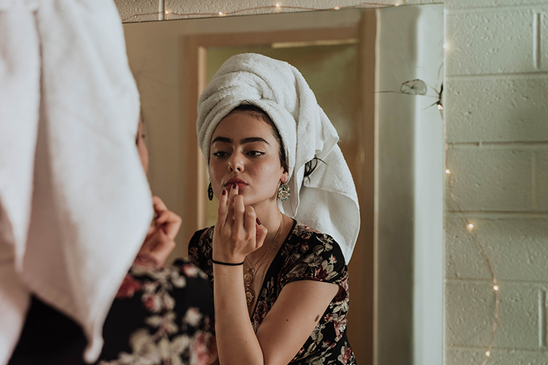 Woman doing her skincare routine in front of a mirror with a towel in her hair.