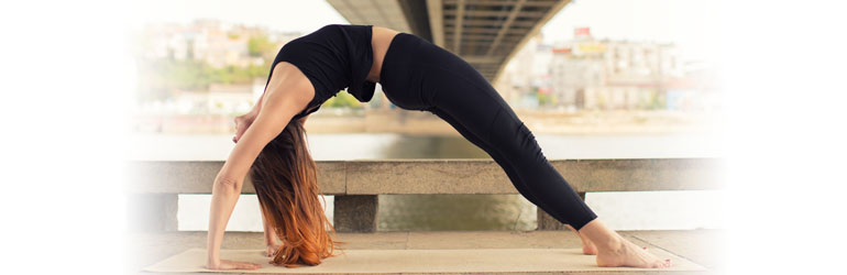 An intermediate level backbend demonstrates someone in a full bridge pose with their arms outstretched.