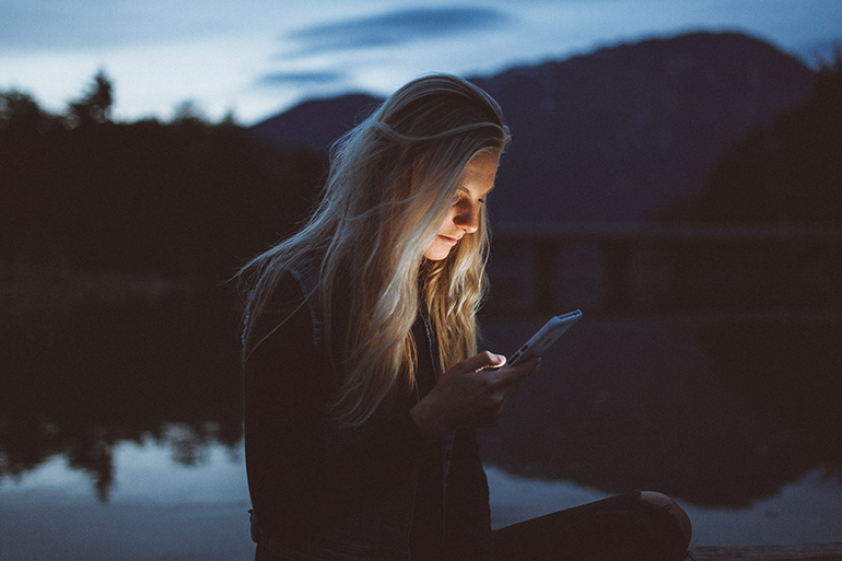 A woman standing by a lake looking at her phone. She has blonde hair and is wearing a black sweater.