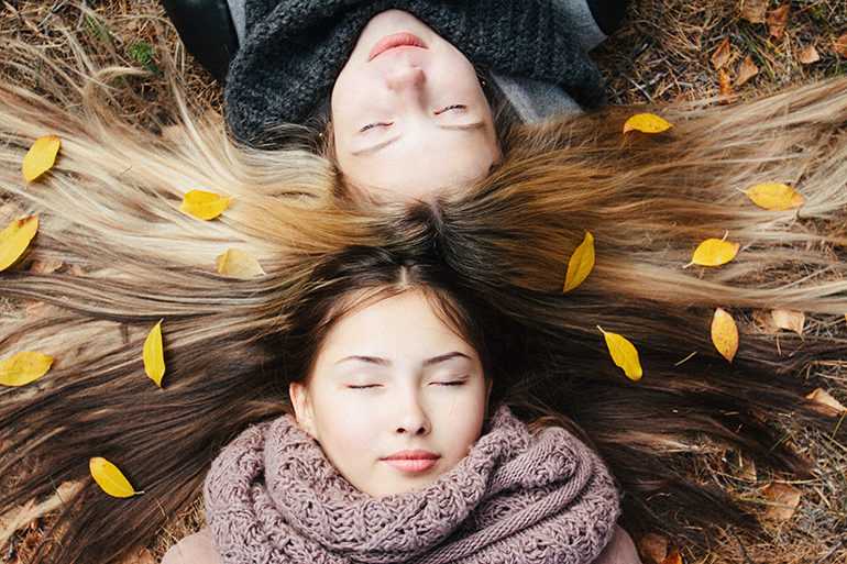 Two women lay down in the autumn leaves. The are wearing cozy scarfs and their hair is splayed out like a lions mane - covered in the leaves.