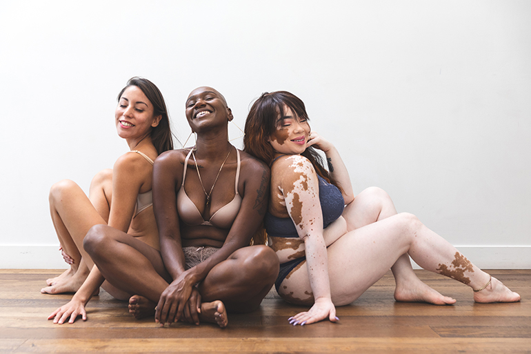 Three femmes with different body types sit together.