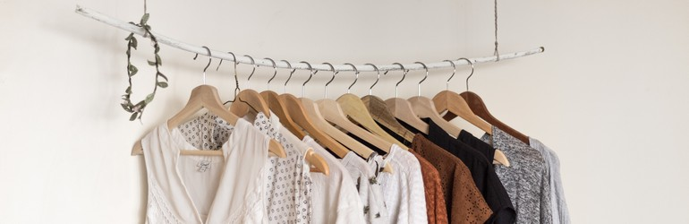 A basic wardrobe hanging against a white wall.