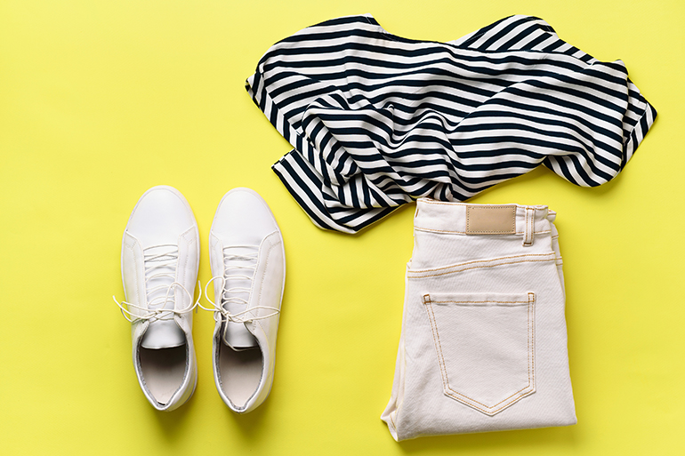 A basic outfit on a yellow background. White shoes, blue jeans, and a black and white striped shirt - all folded nicely.