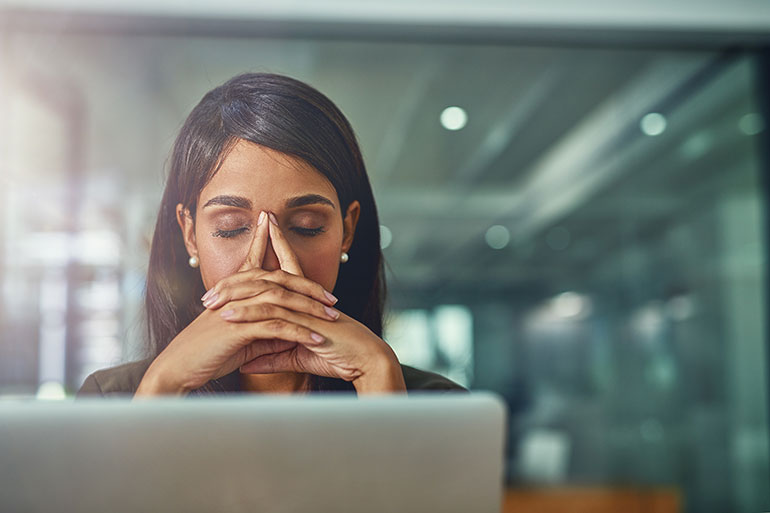 woman with headache in front of laptop