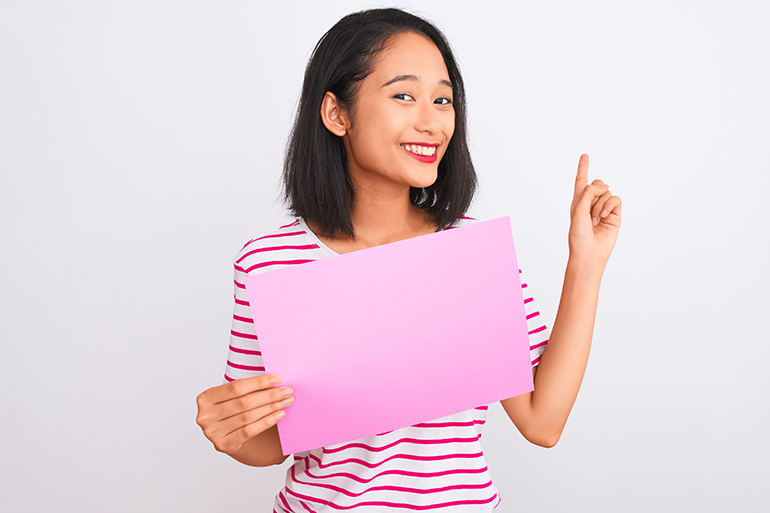 A woman holding a pink piece of paper because she it about to do a craft.