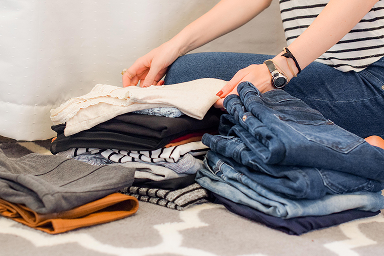 A person is folding a bunch of clothes while kneeling on a white carpet. There is one pile of blue jeans and another of blouses.