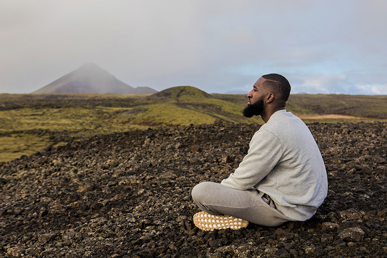 A man sits in a beautiful hilly landscape looking out at the horizon. He is sitting cross legged and away from the camera.