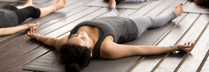 A person lays on their back in a yoga class with their arms and legs stretched out into star pose.